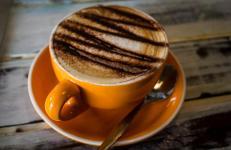 Cappuccino in an Orange Mug with chocolate powder!!! YUM!